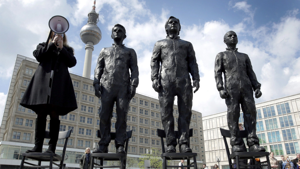 "A women delivers a speech as she stands on a chair of the public art project ""Anything to Say?"" at the Alexander Square in Berlin, Germany, Friday, May 1, 2015. The sculpture of the Italian artist Davide Dormino shows the whistleblowers Chelsea Manning, Julian Assange and Edward Snowden, from right, to honour their courage. (AP Photo/Michael Sohn)"